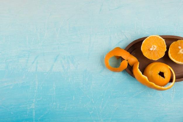 Oranos amarelos descascados em uma travessa de madeira, no lado direito