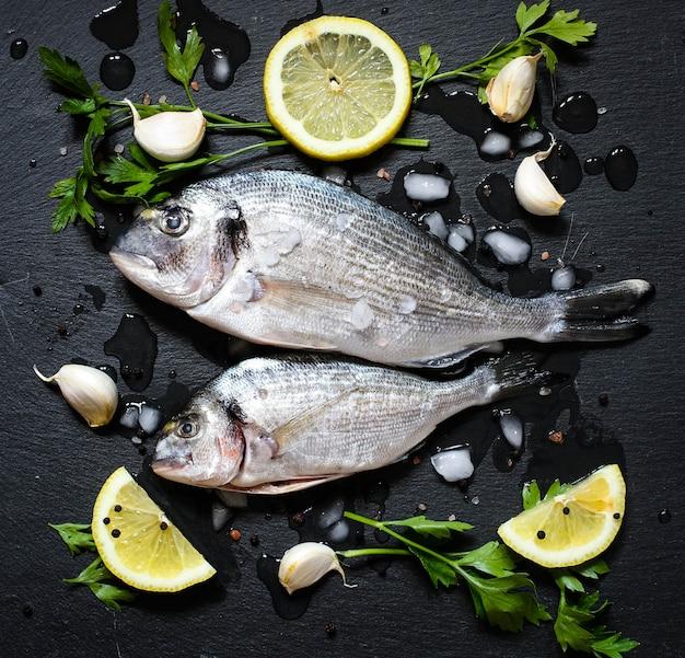 Orata de peixe fresco sobre uma pedra preta com legumes