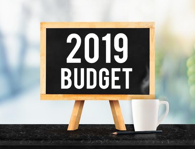 Orçamento de 2019 no quadro-negro com cavalete na mesa de mármore preta com a xícara de café no escritório de borrão