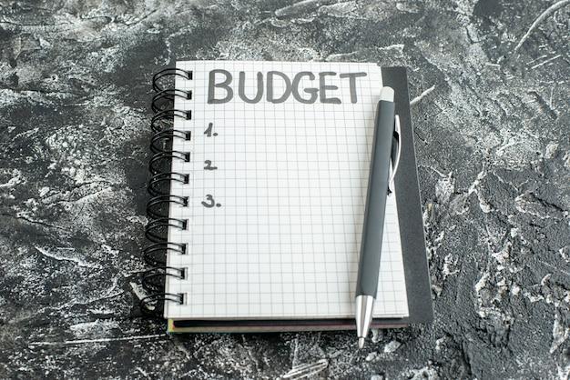 Orçamento de vista frontal escrito nota no bloco de notas com caneta no fundo cinza