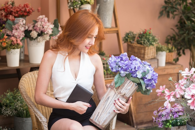 Ordem de verificação bonita de sorriso da mulher de negócio na loja de flor