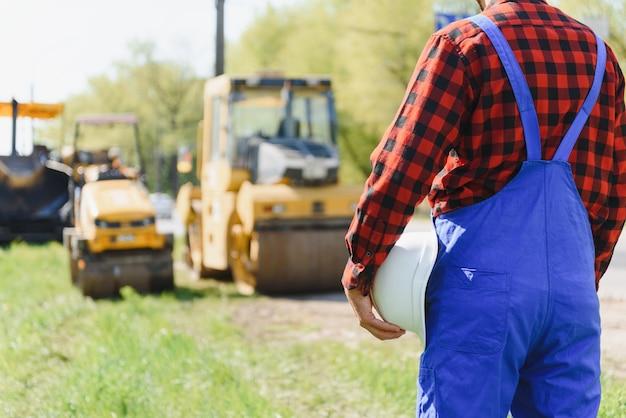 Ordens do engenheiro para que os trabalhadores trabalhem com segurança no canteiro de obras, os trabalhadores colocam asfalto na estrada