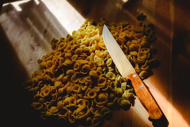 Orecchiette, massa italiana da semolina do trigo, em uma tabela e em uma faca.