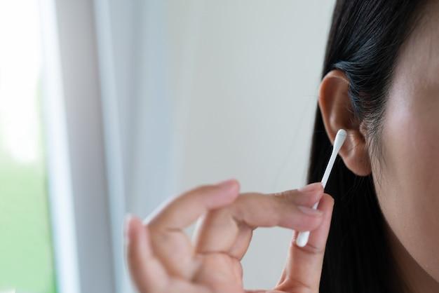 Orelha da limpeza da mulher com cotonete