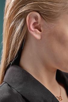 Orelha da loira em close-up de jaqueta preta