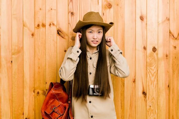 Orelhas da coberta da mulher do jovem viajante chinês com as mãos.