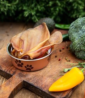 Orelhas de porco secas no recipiente do cão entre a vegetação na placa de madeira. guloseimas de mastigação para cães domésticos.
