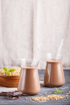 Orgânico não leite de aveia chocolate leite em vidro e placa de madeira com sementes de aveia em um fundo preto de concreto
