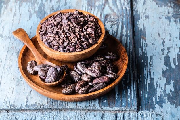 Orgânicos crus grãos de cacau seco, pontas em tigelas de madeira