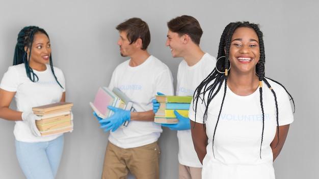 Organização de voluntariado sorridente com livros para doações