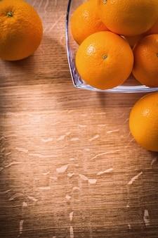 Organizado copyspace frutas laranja na tigela quadrada de vidro na madeira