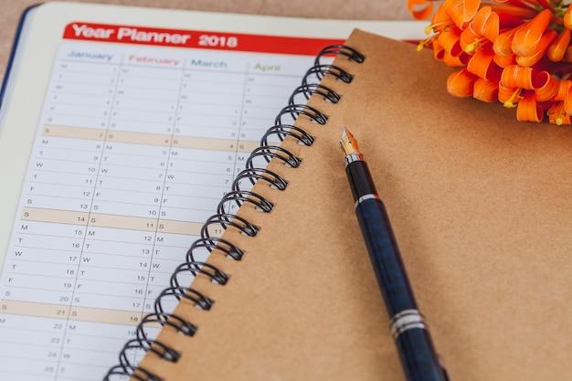 Organizador pessoal ou planejador com caneta-tinteiro na mesa de madeira.