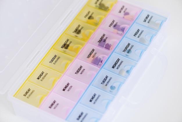 Organizador semanal de comprimidos de plástico com comprimidos em fundo branco