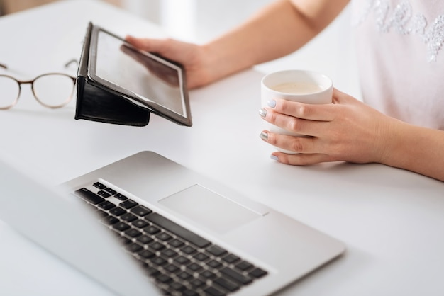 Organizando calendário. senhora profissional dedicada e simpática, usando seus dispositivos, planejando o dia enquanto toma um café no café da manhã
