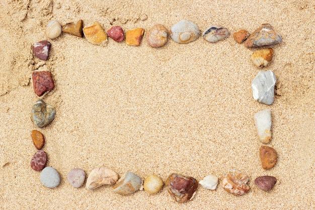 Organizando pedras em areia de praia para o fundo de verão