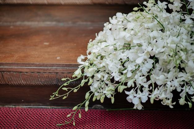 Organize flores com orquídeas brancas.