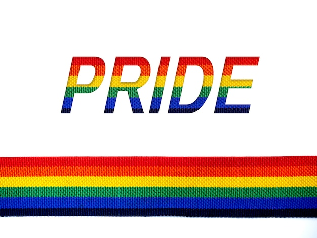 Orgulho, palavras e fita de listra de arco-íris isolada no fundo branco com espaço de cópia. conceito lgbt com cores do orgulho e faixa da bandeira do arco-íris. fundo de banner lgbt.