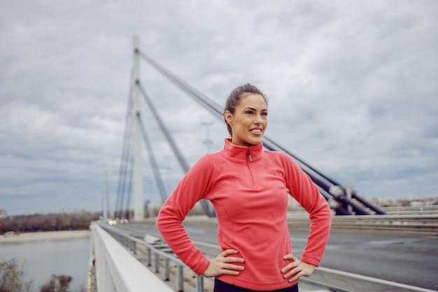 Orgulhosa bonita jovem desportiva morena em pé na ponte com as mãos nos quadris e fazendo uma pausa na corrida. vida urbana. fitness ao ar livre no conceito de tempo nublado.