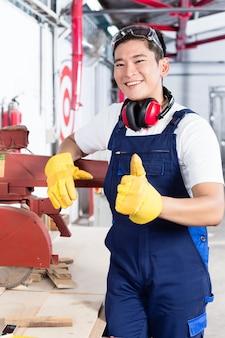 Orgulhoso carpinteiro asiático mostrando os polegares