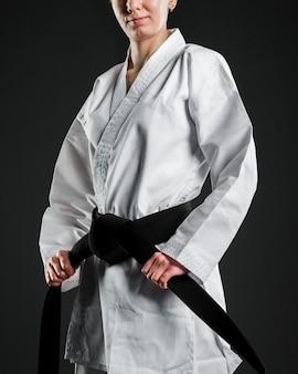 Orgulhoso lutador de karatê segurando faixa preta
