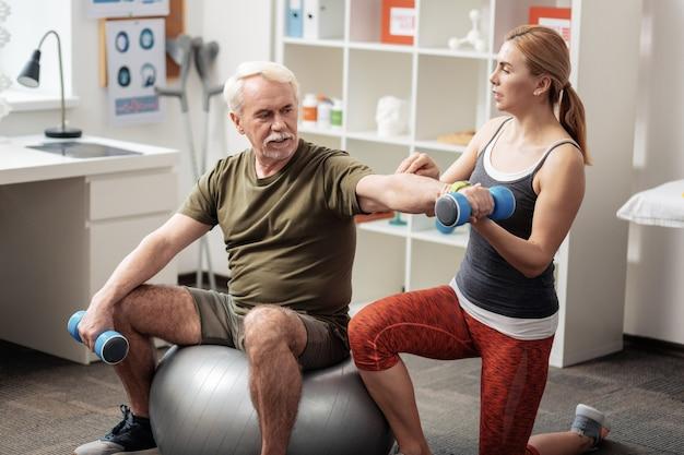 Orientação profissional. agradável treinadora profissional estando com um paciente enquanto o ajuda a fazer o exercício