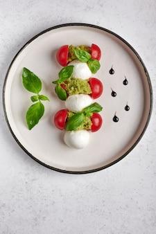 Orientação vertical deliciosa salada caprese italiana com tomates maduros, manjericão fresco e queijo mussarela