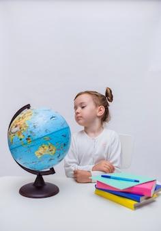 Orientação vertical. uma aluna inteligente se senta em uma mesa e olha para um globo em um branco isolado
