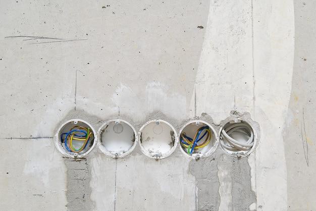 Orifícios na parede de concreto para instalação de caixas plásticas sob os soquetes. instalação de tomadas em parede de concreto e fiação.
