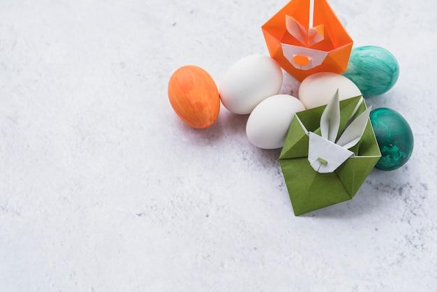Origami de coelhos verdes e laranja e conjunto de ovos de páscoa