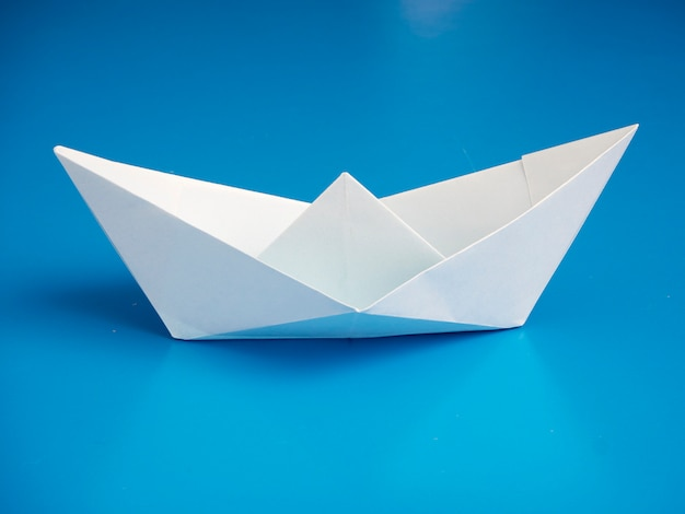 Origami de conceito de negócio papel de barco branco mínimo sobre fundo azul