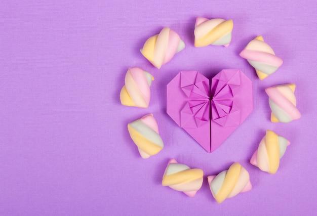 Origami de coração e marshmallow em fundo roxo