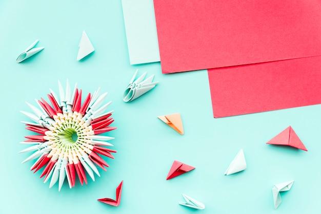 Origami de flor bonita feito com papel vermelho no pano de fundo verde-azulado