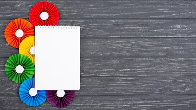 Origami de papel de arco-íris ao lado do caderno