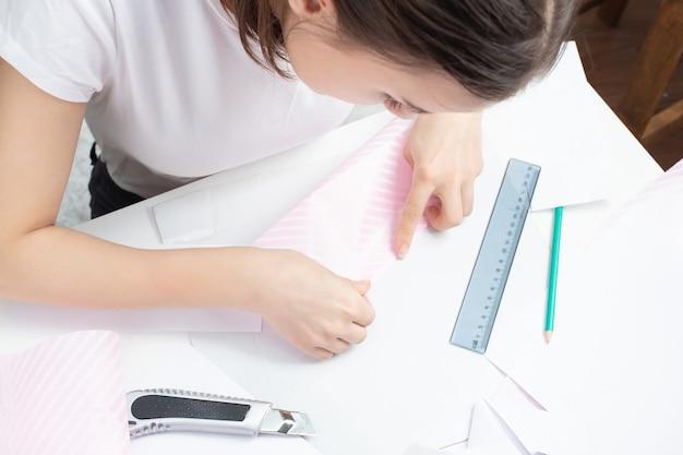 Origami é uma antiga arte chinesa de dobrar papel. menina fazendo um boneco palito