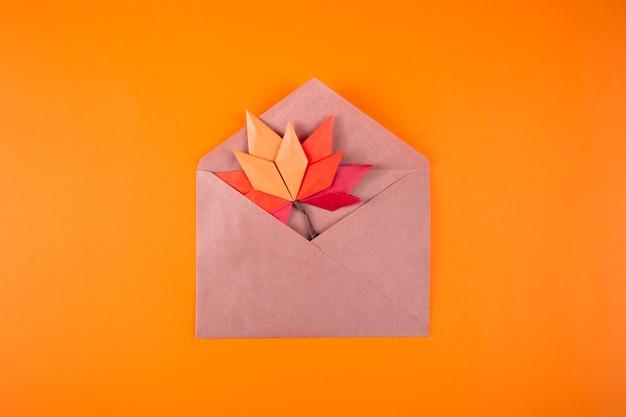 Origami papercraft outono conceito folhas caídas carta em um envelope em uma arte de artesanato artesanal de fundo liso close-up