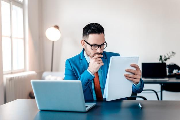 Originais novos concentrados da leitura do homem de negócios na mesa de escritório.