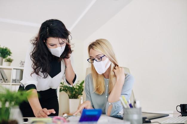 Orking no escritório com máscaras cirúrgicas