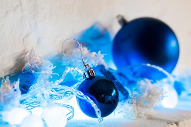 Ornamento azul e prateado de xmas no fundo brilhante do feriado com espaço para o texto. feliz natal! bolas azuis de natal