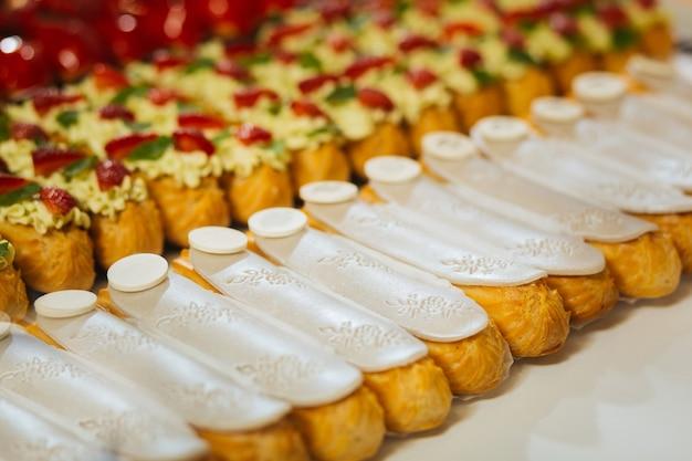 Ornamento branco. close de deliciosos éclairs com sabor de baunilha e chocolate branco por cima