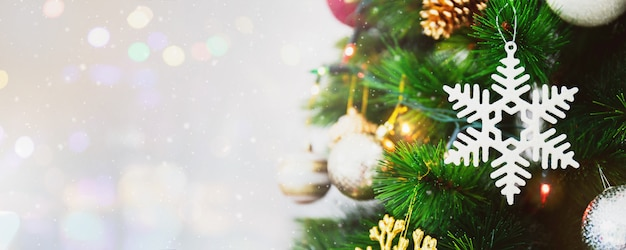 Ornamento da decoração do floco de neve branca no fundo da árvore de natal com queda de neve, bokeh do borrão e espaço da cópia.