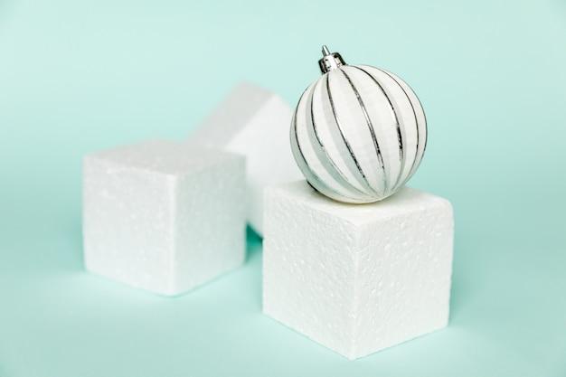 Ornamento de objetos de inverno de composição simplesmente mínima e formas de cubo forma geométrica pódio isolado azul