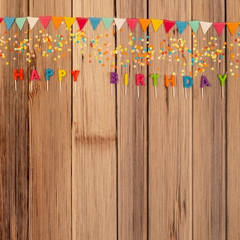 Ornamentos de aniversário plana leigos em fundo de madeira