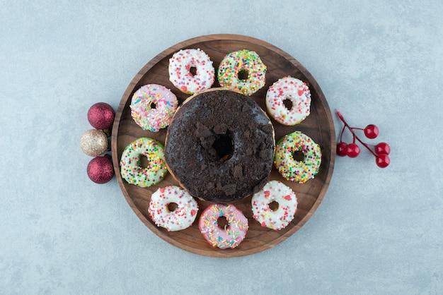 Ornamentos festivos e uma bandeja de pequenos donuts em torno de um único donut grande em mármore.