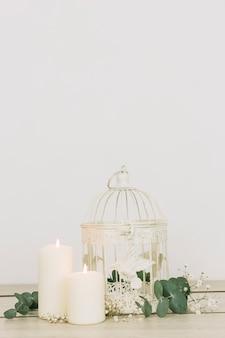 Ornamentos românticos com velas e gaiola
