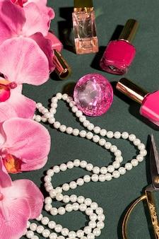 Orquídea rosa ao lado de itens de garota fashion