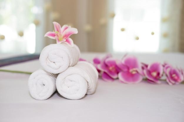 Orquídea rosa bonita na toalha branca no salão de spa.