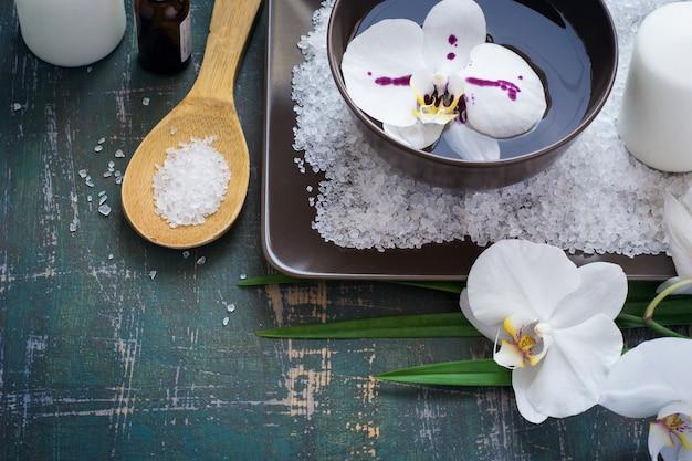 Orquídeas brancas da flor na bacia de água e no ajuste dos termas.