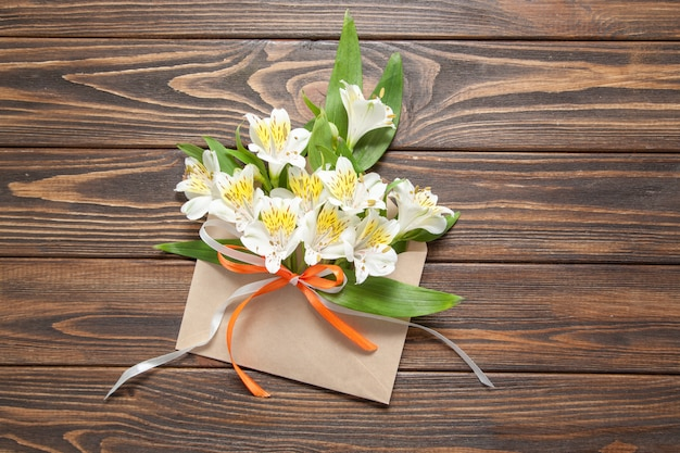 Orquídeas pequenas das flores brancas macias em um envelope esperto do correio em um fundo de madeira