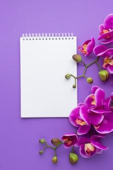 Orquídeas roxas com o bloco de notas do espaço da cópia