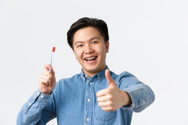 Ortodontia, atendimento odontológico e conceito de higiene. close-up de asiático feliz satisfeito segurando a escova de dentes, sorrindo com aparelho dentário e mostrando o polegar para cima em aprovação, fundo branco.